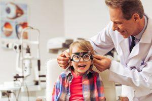 A man optometrist doing an eye test on a little boy
