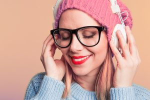 A pretty blonde woman wearing glasses smiling and listen to headphones